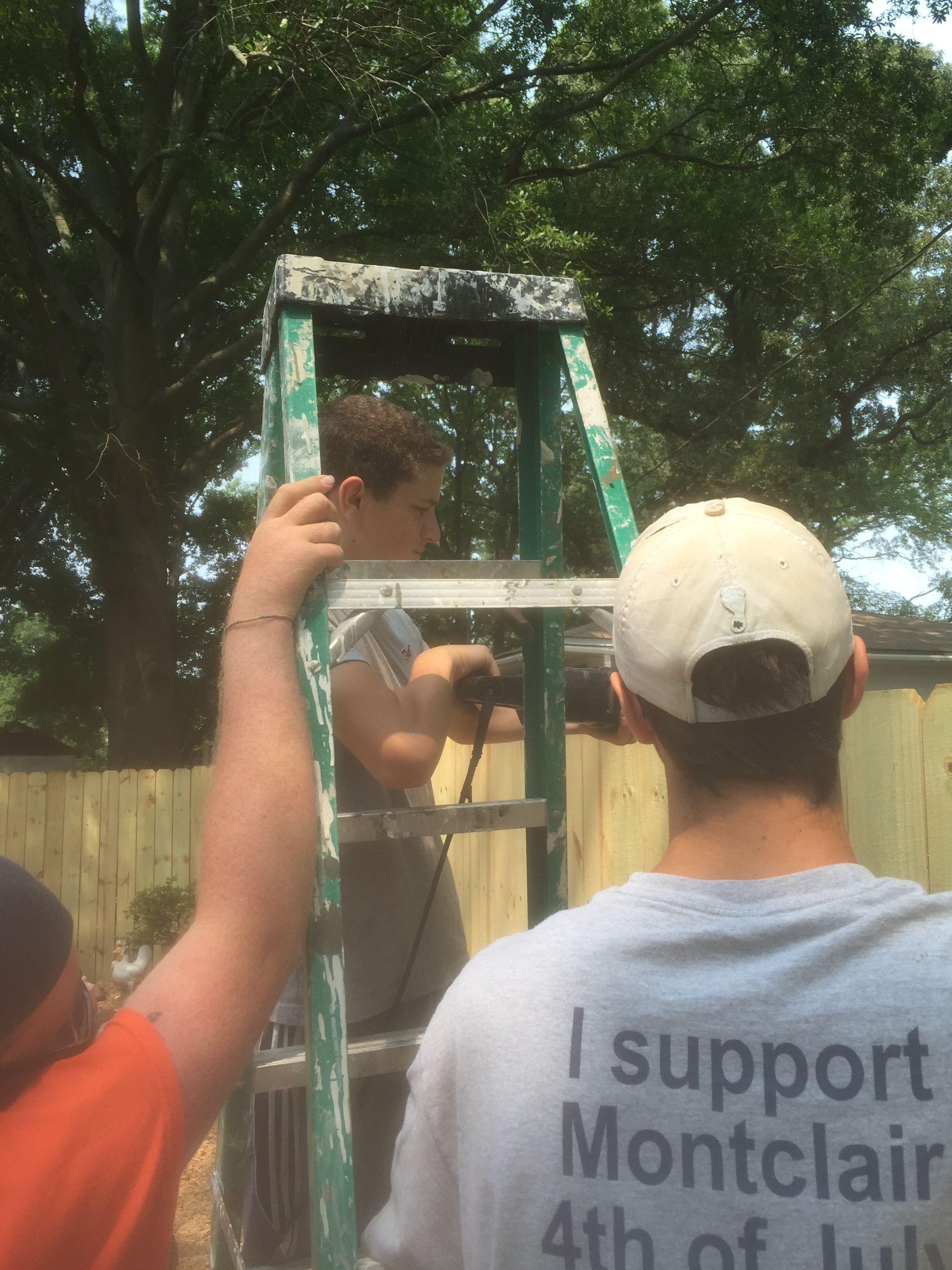 Austin Brown helps repair a fence while others assist